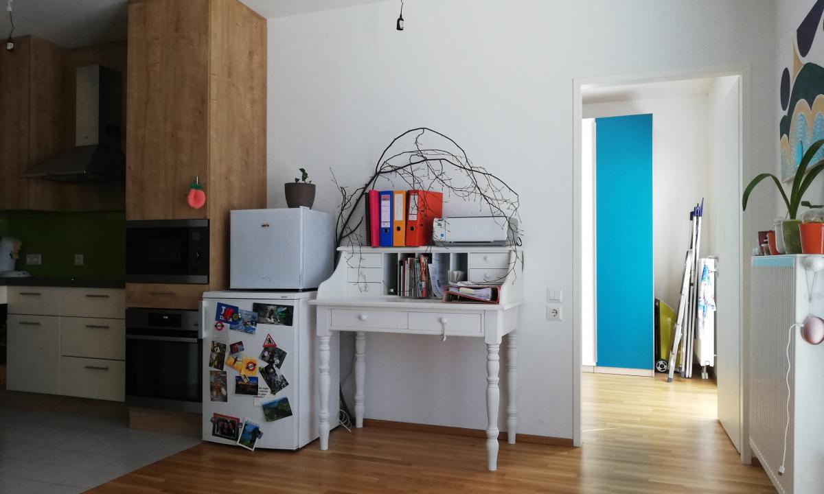 Teil des Wohnbereichs ist der weiße Sekretär-Tisch, auf dem Bild ebenfalls enthalten ist die Tür zum Schlafzimmer