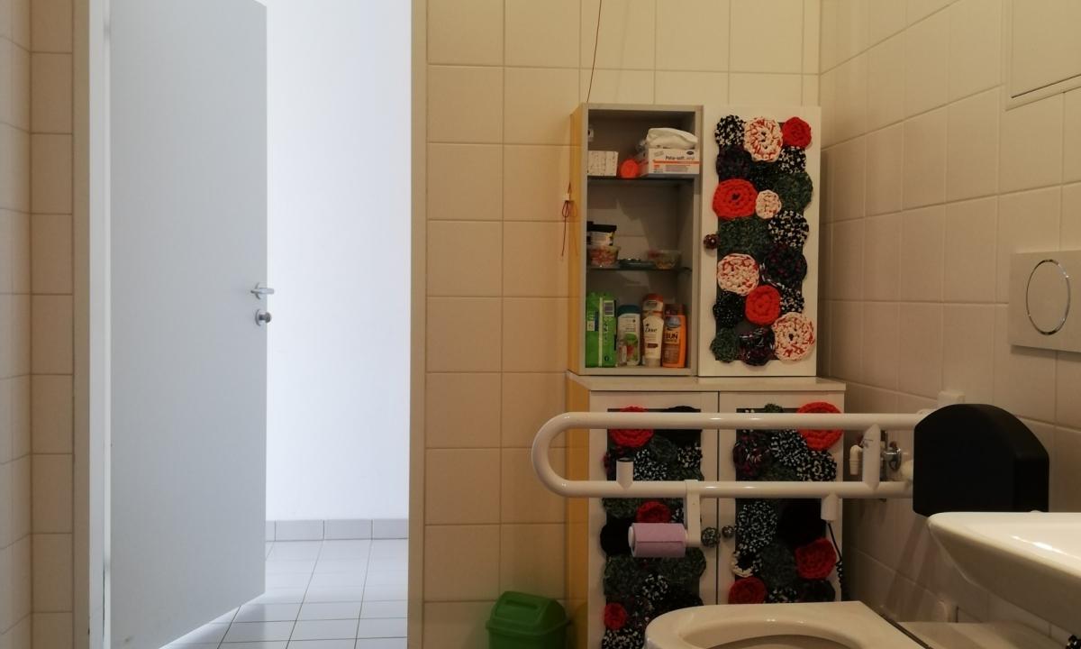 Barrierefreies Badezimmer mit Waschbecken, Toilette, Schrank im Bild