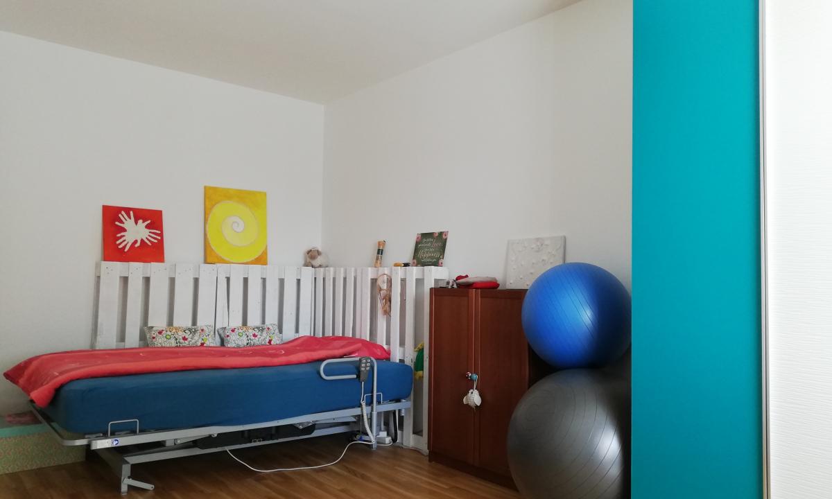 Schlafzimmer mit elektrisch verstellbares Bett, Gymnastikbällen und Schrank
