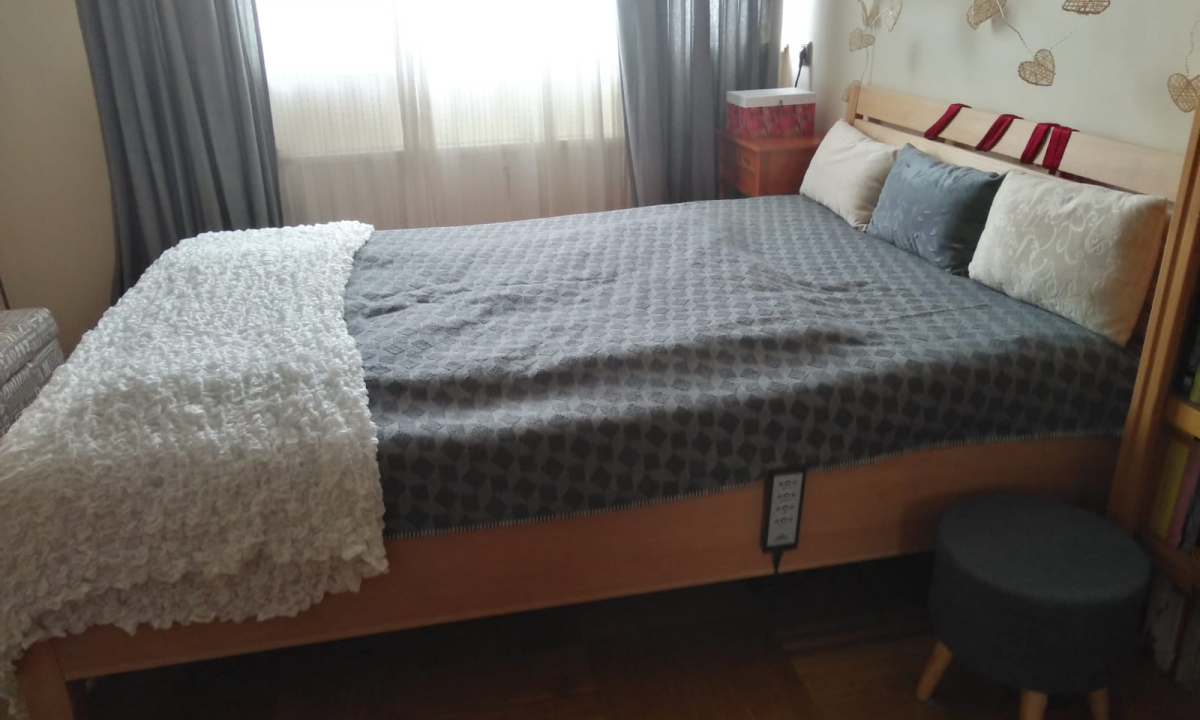französisches Bett, frisch bezogen, großes Fenster mit Store und Vorhang